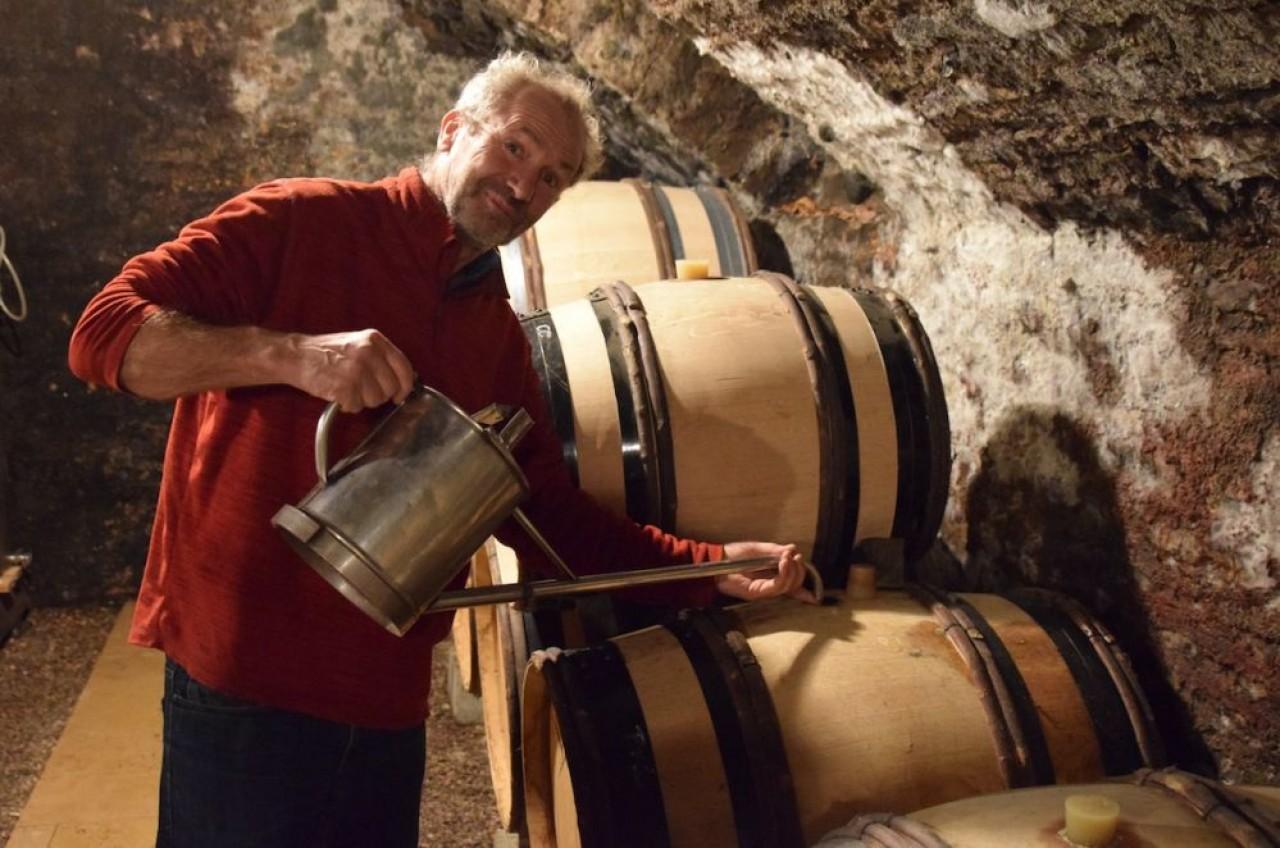 Franck Follin-Arbelet, vigneron à Aloxe-Corton (Côte-d'Or), en train d'ouiller un de ses tonneaux, c'est-à-dire compenser l'évaporation en rajoutant du vin. © Traces Ecrites