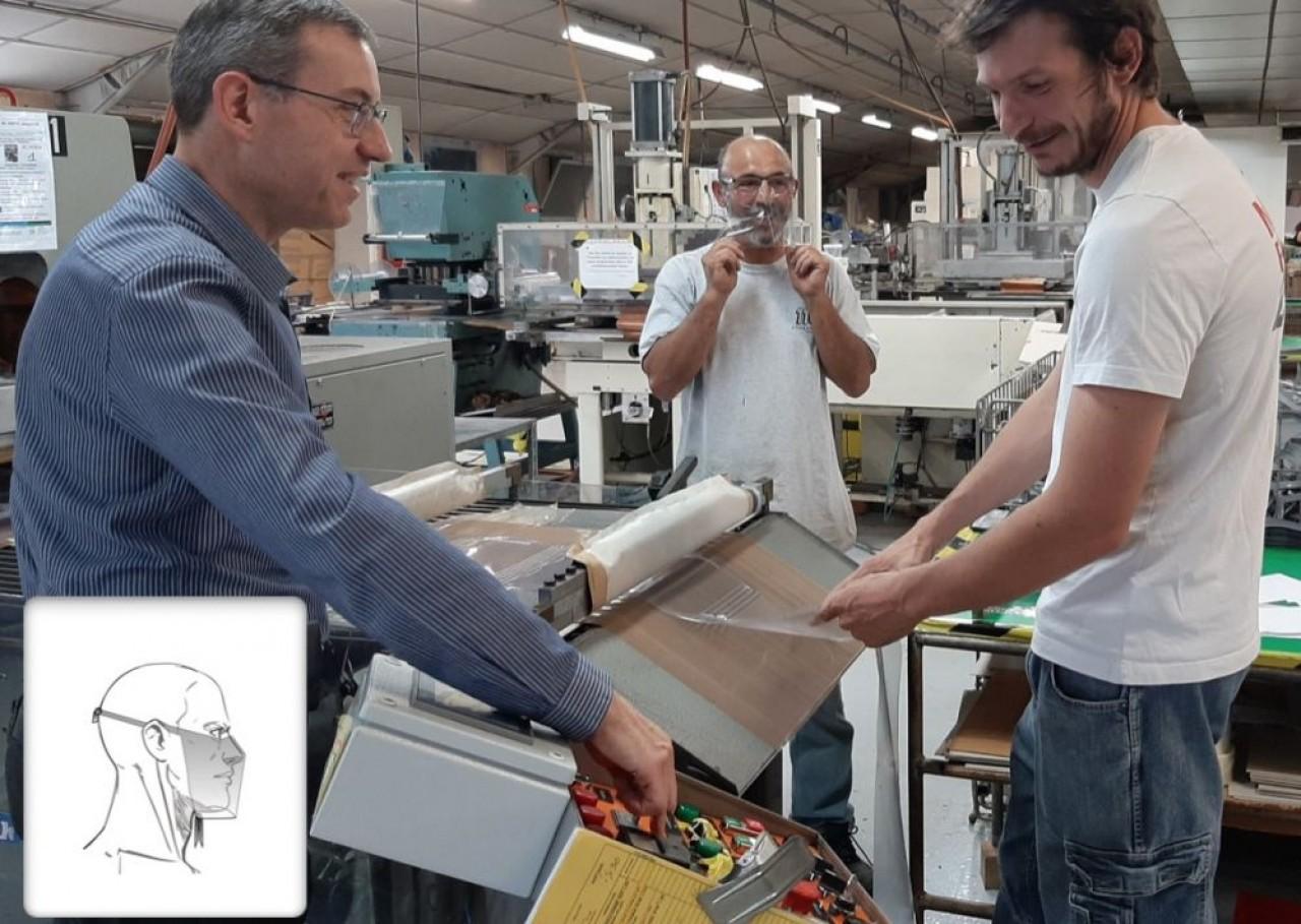 Christophe Bertrand (à gauche), PDG de Simon et ses responsables de production, Carlos Batista Mendès et Jean-Baptiste Duban devant une machine à découper les masques à partir d'une plaque de vinyle ultra fine.