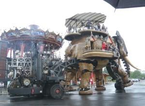 Un ingénieux système de mécanismes donne vie à l'éléphant géant en bois exotique.